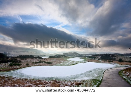 View from the tee of a golf course in Scotland on a snowy winter morning, with dramatic cloudy sky overhead. - stock photo