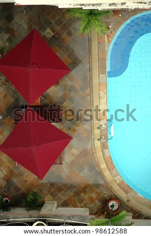 view from the top of beautiful swimming pool with two red tent - stock photo