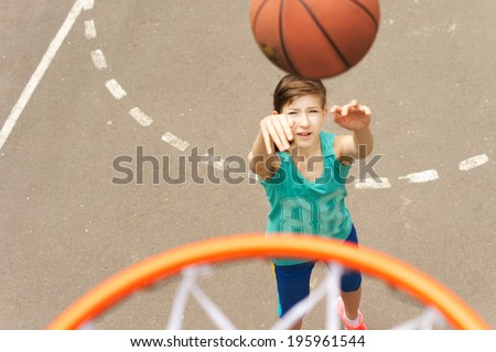 View from the top of the hoop of a young teenage girl practicing her basketball throwing the ball at the net trying for a goal