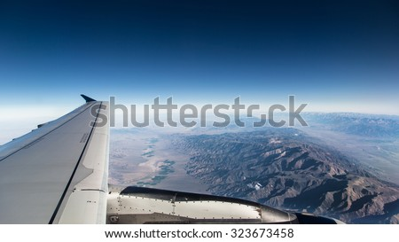 View from the wing of a plane, a ridge overrated, with little clouds.  - stock photo