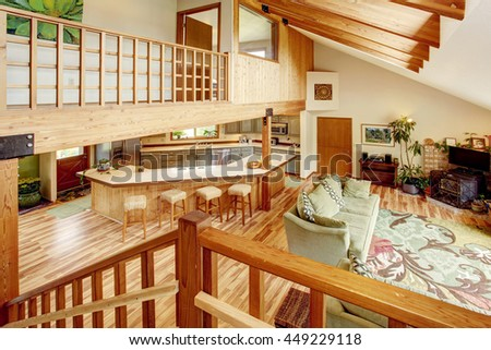 View from the wooden staircase into the living room and kitchen room. Wooden beams on the ceiling.