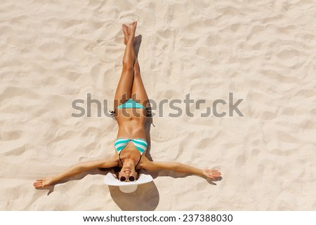 View from top of beautiful girl in bikini wearing white hat and sunglasses on beach sand in summer - stock photo