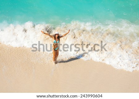 View from top of girl with white hat in striped bikini standing in ocean waves on the sand of beach during holidays summer time - stock photo