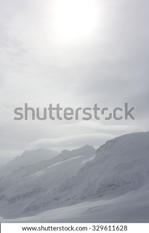 View from top of snow covered mountain. jungfrau mountain in swiss alps - stock photo