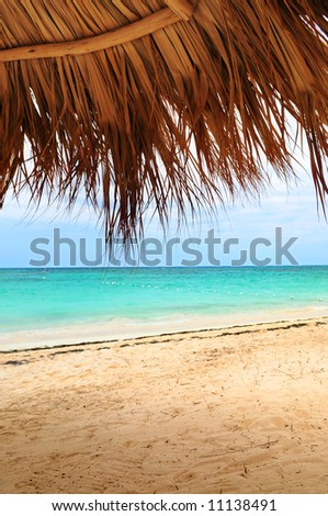 View from under palm leaves shelter onto tropical beach of a Caribbean island - stock photo