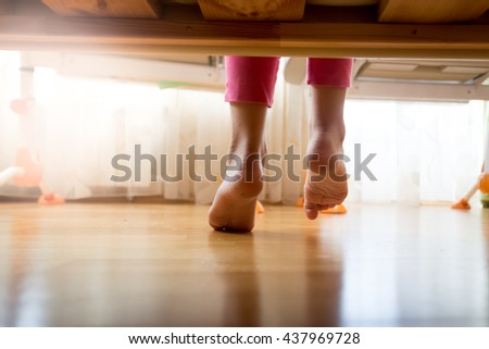 View from under the bed on girl stepping on wooden floor at bedroom - stock photo