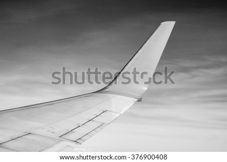 View from window seat  looking at aircraft wing flying over clouds with black and white color - stock photo