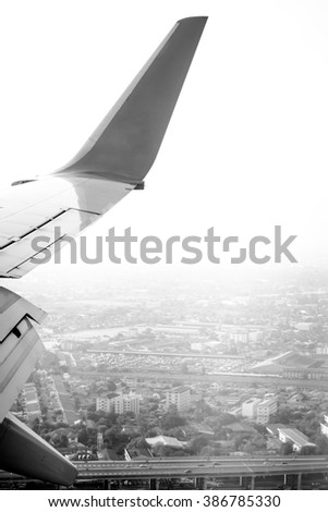 View from window seat  looking at aircraft wing flying with city view prepare for landing on black and white color - stock photo