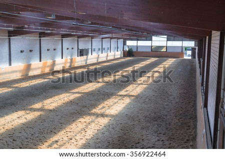 View in an indoor riding arena. The riding school is suitable for dressage horses. - stock photo
