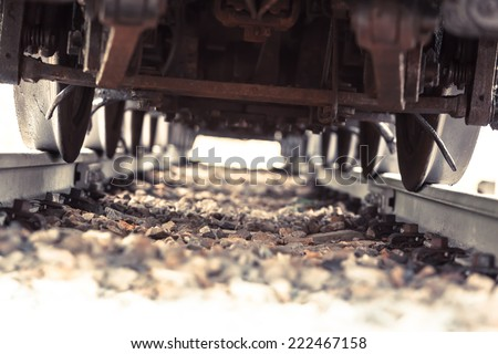 View inside a railroad track under a heavy steam locomotive with many wheels/ Train Run Over - stock photo