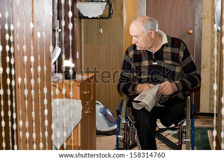 View into a room of a disabled elderly man sitting in his wheelchair staring thoughtfully down at something with his rolled up newspaper in his hands, candid image - stock photo