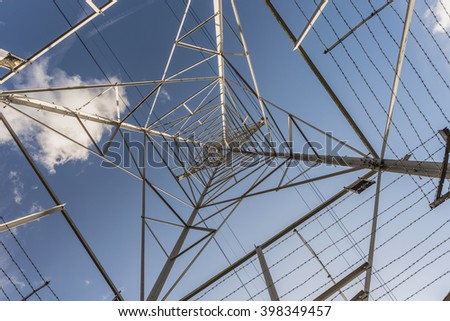 View looking up through an electricity pylon on  a sunny day