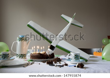 View of a airplane model flown into birthday cake - stock photo