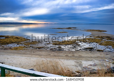 View of a beach with a handrail in the foreground and stormy skies above at dawn at Penobscot Bay in Searsport, Maine - stock photo
