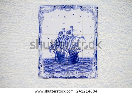 View of a beautiful decorated azulejo tile depicting a Portuguese caravel ship. - stock photo