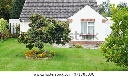 View of a Beautiful Garden Lawn and Cottage  - stock photo