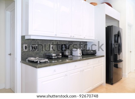 View of a beautiful modern kitchen with upscale appliances, white cabinets, and green granite counter tops - stock photo