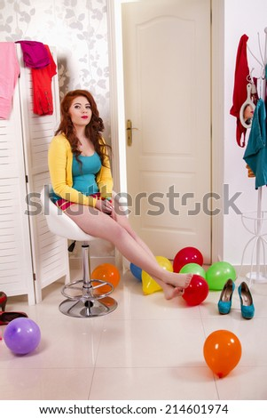 View of a beautiful redhead girl in her colorful bedroom. - stock photo