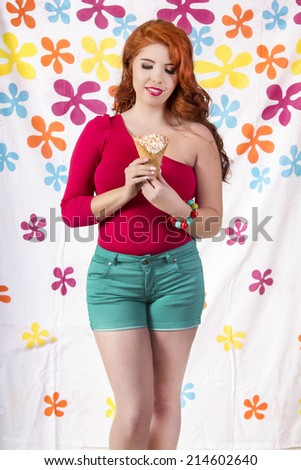 View of a beautiful redhead girl wearing colorful clothing holding an ice cream.
