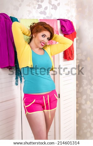 View of a beautiful redhead girl with colorful clothes in her bedroom.