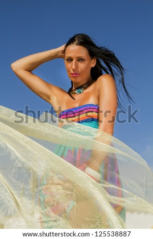 View of a beautiful woman in a colorful dress in the beach, bathed by the sunny rays of Summer.