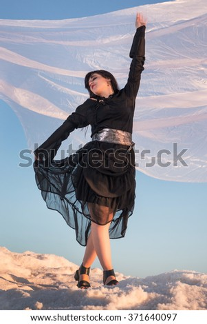 View of a beautiful young girl in gothic clothing on a salt hill.