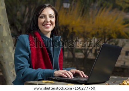 View of a beautiful young woman working on a laptop on a urban park.