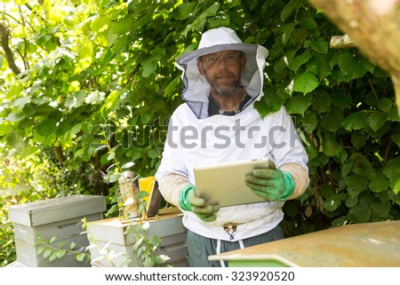 View of a Beekeeper handling a tablet in front of beehives