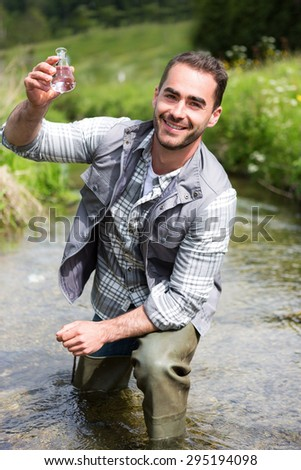 View of a Biologist take a sample in a river in order to do some test