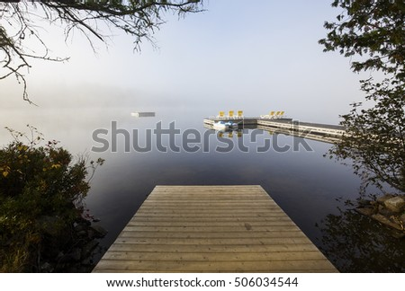 view of a boat dock the Lac-Superieur, misty morning with fog, in Laurentides, Mont-tremblant, Quebec, Canada