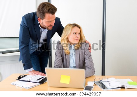 View of a Boss putting hand on assistant shoulder - harrasment