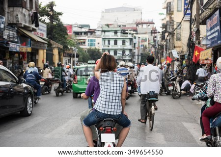 View of a busy street on a weekday in Hanoi, Vietnam. People are seen riding on motorbikes, cycles and cars  to their destinations. Market shops are seen on the background.