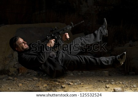 View of a contracted type killer agent in middle air with a machine gun. - stock photo