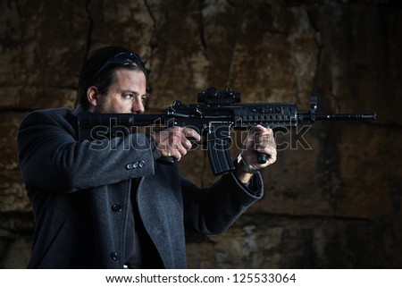 View of a contracted type killer agent wandering with a long jacket and machine gun.