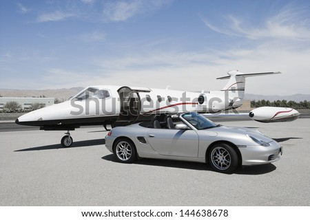 View of a convertible and private jet on landing strip in airport - stock photo
