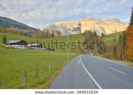 View of a country road passing by a farm land with a church on top of the hill and Mountain Hochkoenig lighted up by alpenglow in the background in Dienten, Austria ~ Beautiful countryside scenery - stock photo