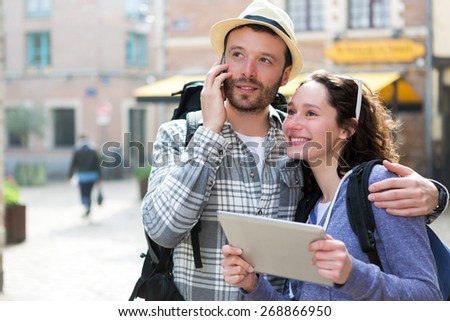 View of a Couple of attractive tourists using tablet and smartphone