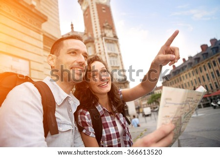 View of a Couple of young attractive tourists watching map  - stock photo