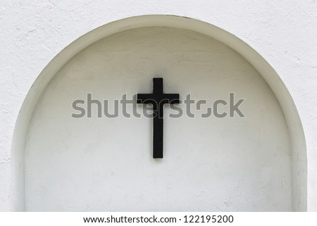 View of a cross sign on arched white wall. - stock photo