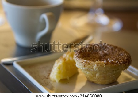 View of a cup of coffee with a portuguese custard tart.