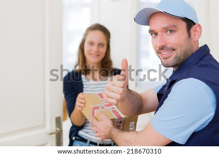 View of a Delivery man handing over a parcel to customer - stock photo