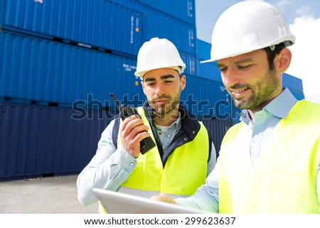 View of a Dock worker and supervisor checking containers data on tablet