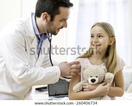 View of a Doctor listening heart beatment of little girl