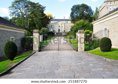 View of a Driveway and Gated Entrance of Old English Residential Buildings - stock photo