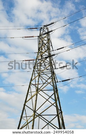 View of a Electricity Pylon against a Blue Cloudy Sky