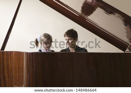 View of a female student and teacher playing piano - stock photo