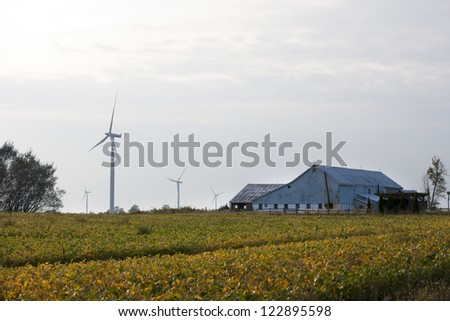 View of a field with barn and wind in the background. - stock photo
