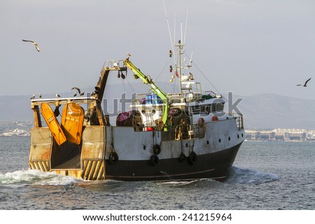 View of a fishing ship exiting through Ria Formosa marshlands, located on Faro, Algarve. - stock photo
