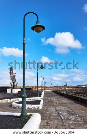 View of a footpath paved with slabs of green street lanterns running along the ocean on the island of Lanzarote, one of the Canary Islands                 - stock photo