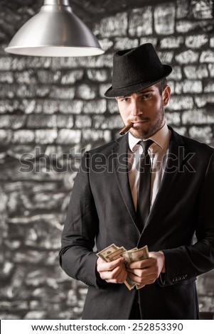 View of a gangster man is smoking a cuban cigar and holding money. - stock photo